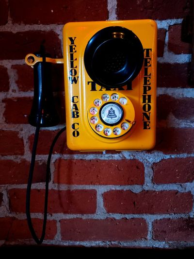 Close-up of telephone booth on brick wall