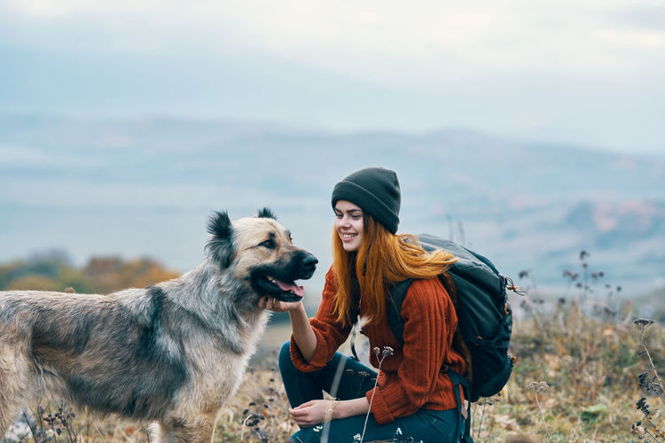 Young woman with dog standing against the sky