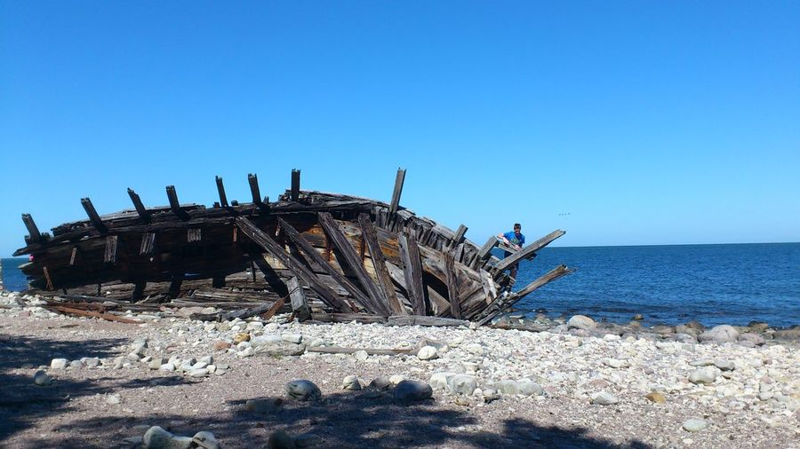 Man Standing By Shipwreck On Sea Shore Against Clear Sky