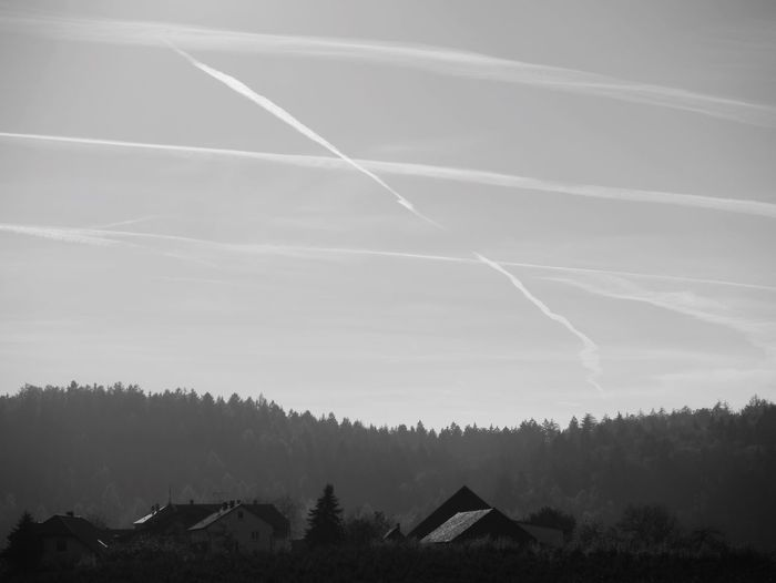 Houses and mountains against vapor trails in sky