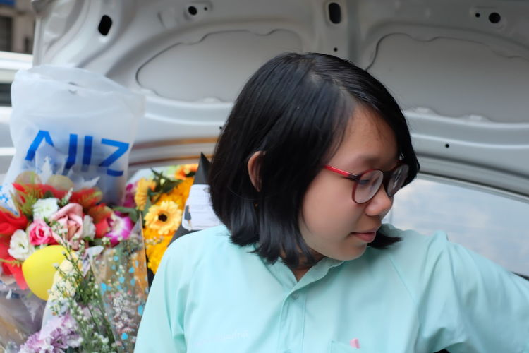 Close-up of young woman in car trunk