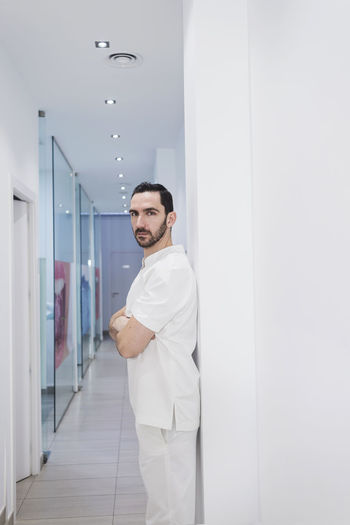 Doctor with arms crossed standing in corridor at hospital