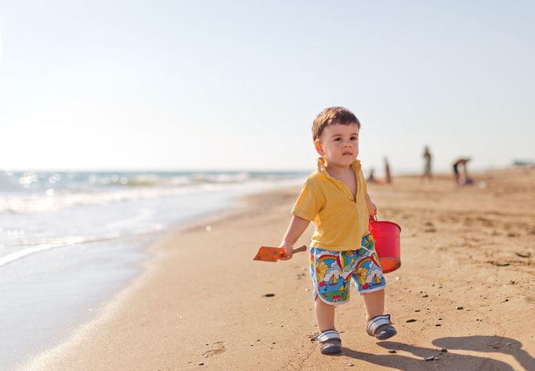 Cute boy carrying bucket at beach