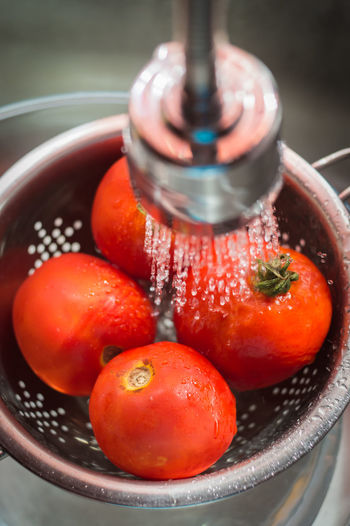 High angle view of tomatoes in strainer under sink faucet