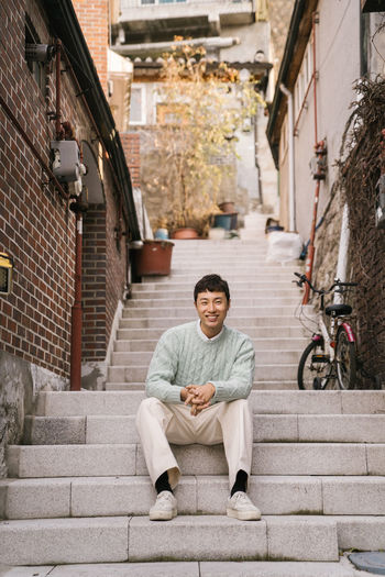 Portrait of smiling man sitting on staircase in city