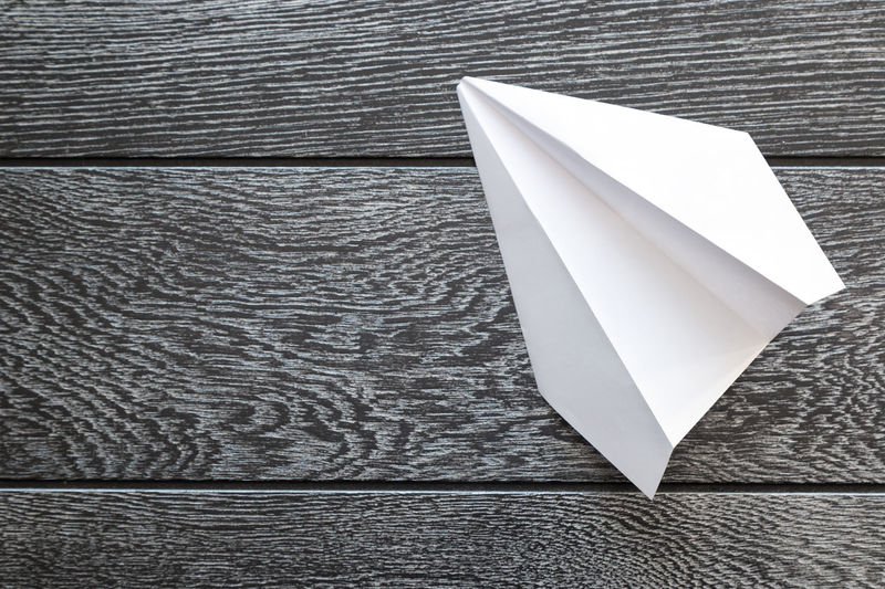 High angle view of paper airplane on wooden table