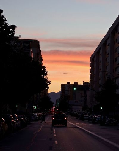Traffic on city street at sunset