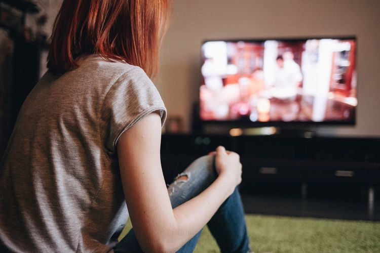 Close-Up Of Young Woman Watching Tv