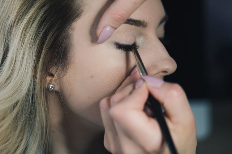 Cropped Hands Applying Eyeliner To Woman