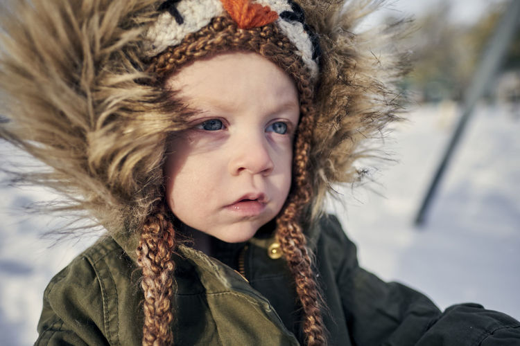 Close-up of cute girl in warm clothing on snow