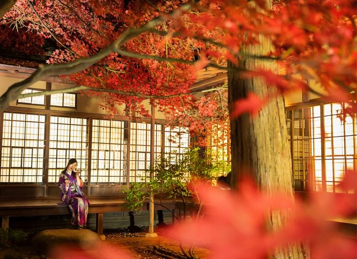 Woman sitting outside house during autumn