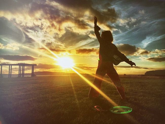 Daughter preparing to cartwheel during a sunset Cartwheel Sunset Clouds And Sky Daughter Field Pose