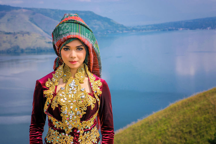 Portrait of beautiful woman wearing traditional clothing while standing on mountain against lake