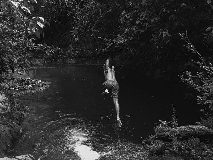 Man Jumping In Lake Against Trees