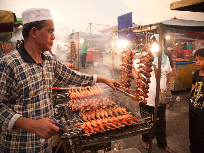 BBQ chicken wing vendor at the unparalleled Kota Kinabalu Night Market Night Market Chicken Wings Kota Kinabalu Adult Barbecue Day Food Food And Drink Freshness Market Market Stall Meat One Person Outdoors People Preparation  Real People Retail  Food Stories An Eye For Travel HUAWEI Photo Award: After Dark #urbanana: The Urban Playground
