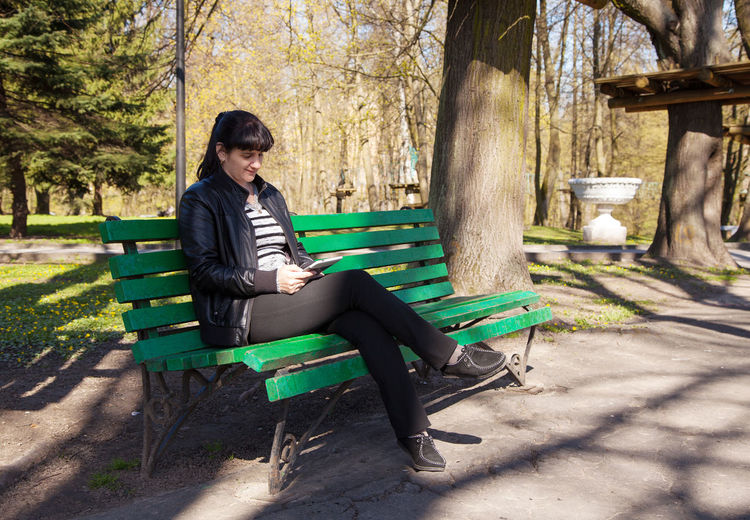 Woman using mobile phone while sitting on bench in forest