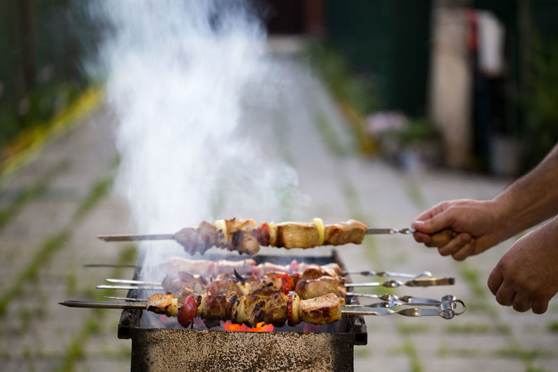 Barbecue Barbecue Grill Close-up Coal Coal Fire Cooking Food Fried Fried Food Group Of Objects Hands Heat - Temperature Holding Leisure Activity Meal Meat Onion Pork Preparation  Ready-to-eat Side By Side Skewers Smoke Smoke - Physical Structure Tomato