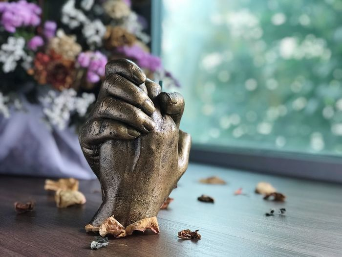Sculpture Of Hands With Dried Petals On Table