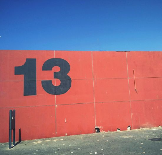 Number 13 On Red Wall Against Blue Sky