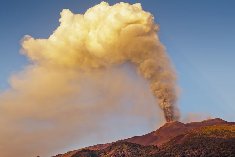 Low Angle View Of Smoke Emitting From Volcanic Mountain Against Sky