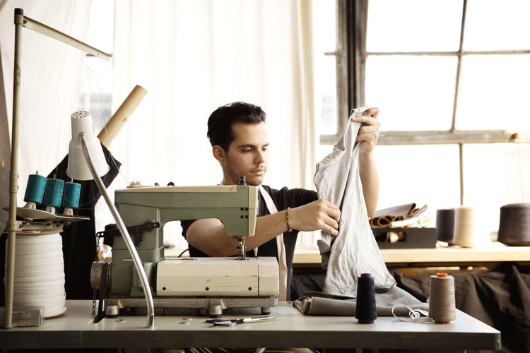 Fashion designer examining gray fabric while working at workshop