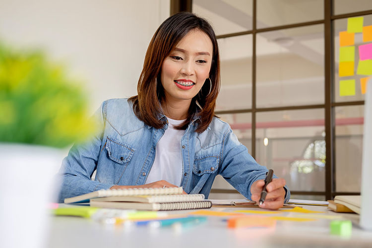 Low angle view of smiling businesswoman working at desk in office