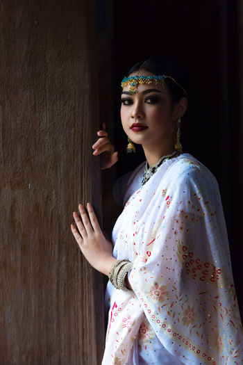 Portrait of beautiful woman in sari standing by wall