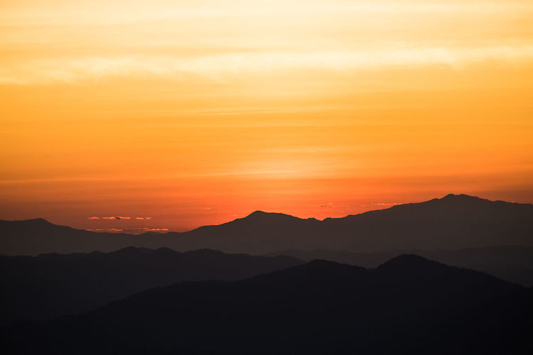Scenic view of silhouette mountains against romantic sky at sunset