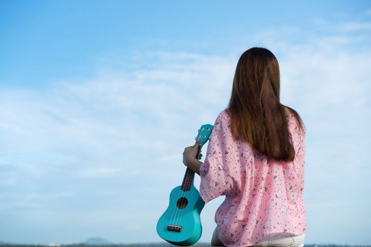 Rear view of woman holding ukulele while sitting against sky