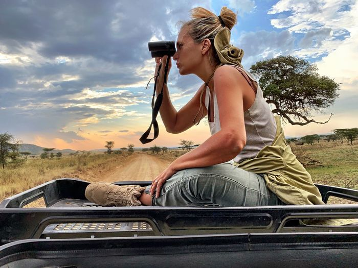 Side view of woman looking through binoculars while sitting on car roof against sky