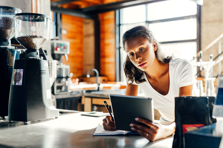 One Person Real People Business Occupation Working Indoors  Food And Drink Modern African American Job Working Owner Standing Morning Digital Tablet Looking Lifestyles Cafe Coffee