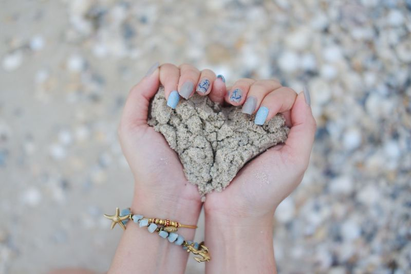 Cropped Hands Of Woman Holding Sand