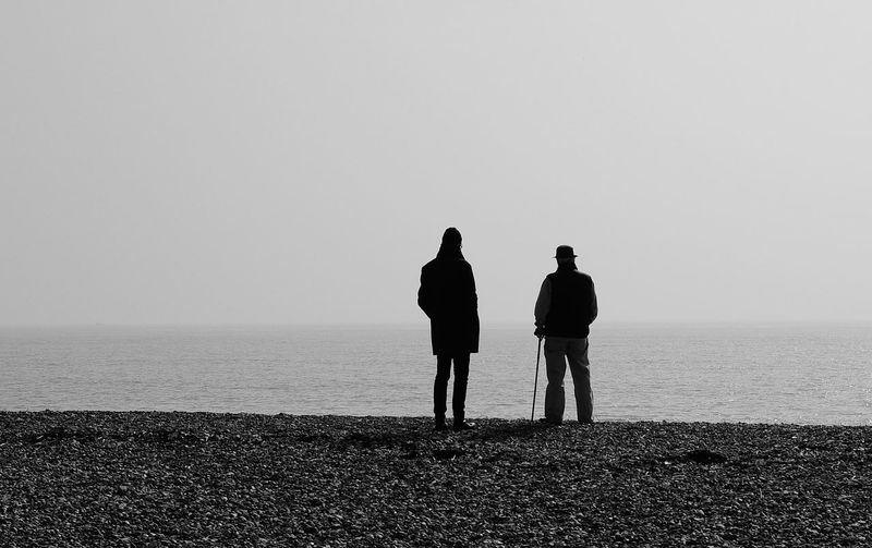 Rear View Of People Standing At Beach