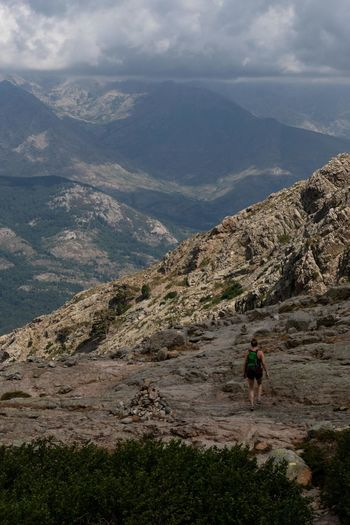 Rear view of man hiking on mountain against sky