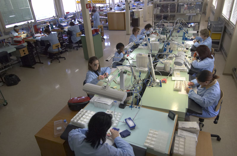 High Angle View Of Watch Makers Working In Industry