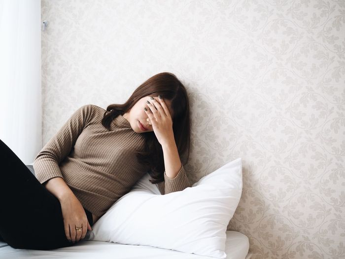 Woman With Headache Leaning On Bed At Home