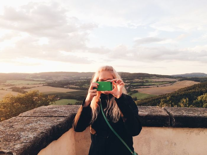 Young woman photographing on mobile phone against sky