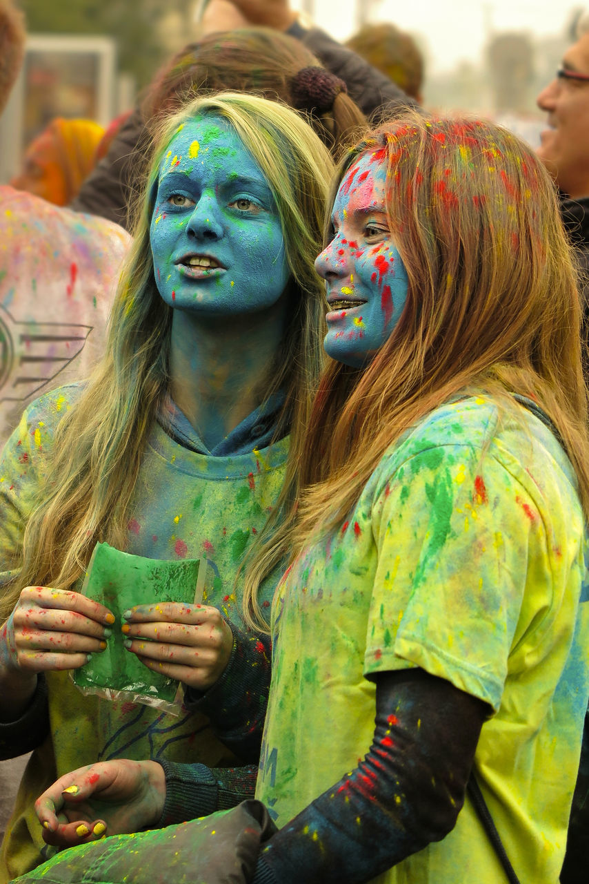 real people, celebration, lifestyles, traditional festival, face paint, leisure activity, togetherness, holi, cultures, fun, focus on foreground, multi colored, happiness, day, young women, outdoors, bonding, powder paint, young adult