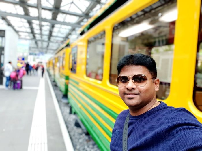 Portrait of smiling man standing by train at railroad station