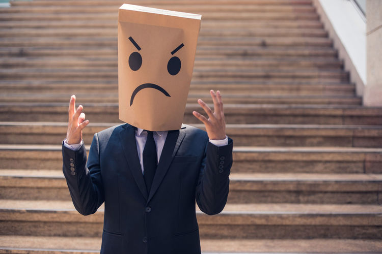 Businessman wearing angry paper mask on steps in city