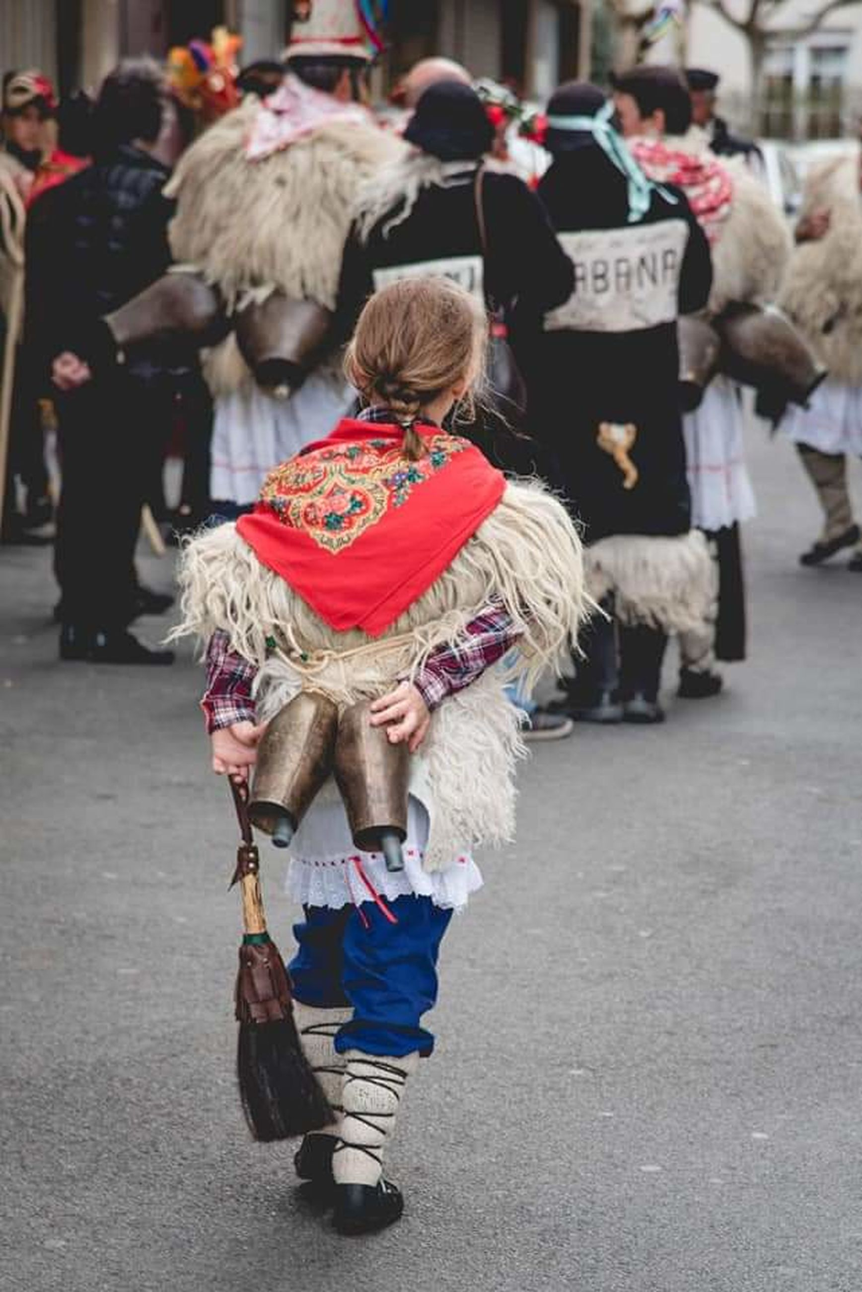 city, street, festival, tradition, full length, group of people, adult, arts culture and entertainment, architecture, crowd, clothing, costume, carnival, traditional clothing, rear view, men, women, celebration, walking, road, large group of people, day, outdoors, person, event, footwear