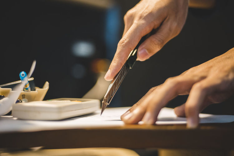 Cut Work Working Working Hard Body Part Book Business Cutter Finger Food And Drink Hand Holding Human Body Part Human Hand Indoors  Men Occupation One Person Paper Paperwork Pen Selective Focus Table Working Writing