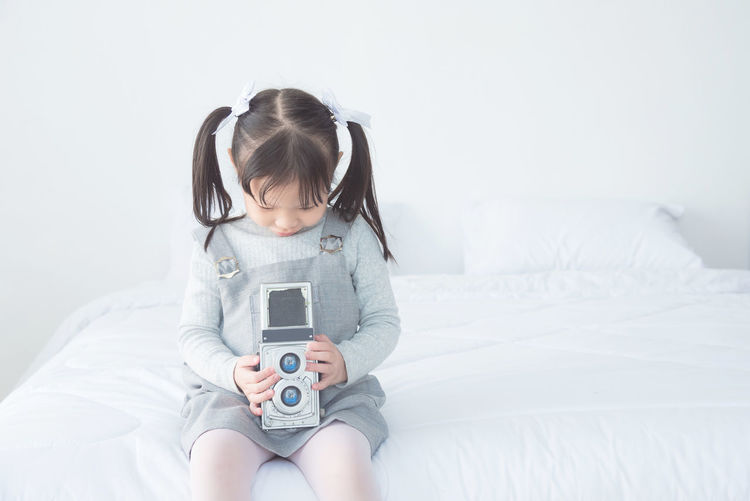 Girl holding camera while sitting on bed at home