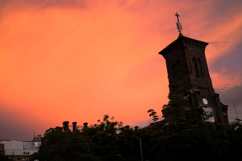 Low angle view of tower against orange sky