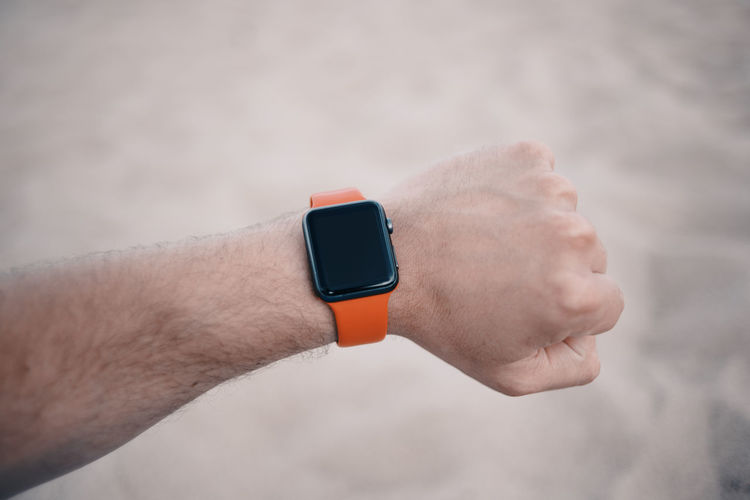 Checking smart watch with red band Hour Red Relaxing Beach Checking The Time Connection Fingers Hand Human Hand Sand Smart Watch Time Watch