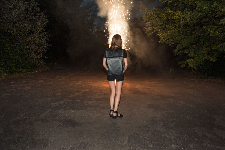 Rear view of young woman standing by illuminated firework on road at night