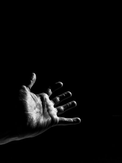 Close-up of person hand against black background