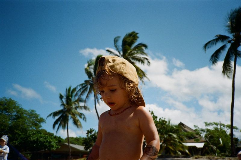 Full length of shirtless boy looking at camera against sky