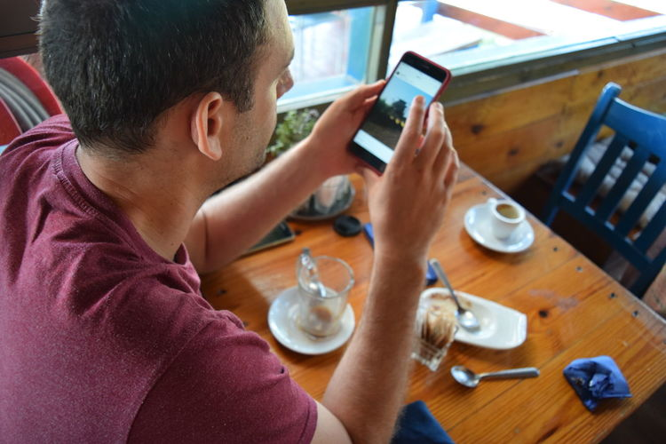 Rear view of man using mobile phone at table in cafe