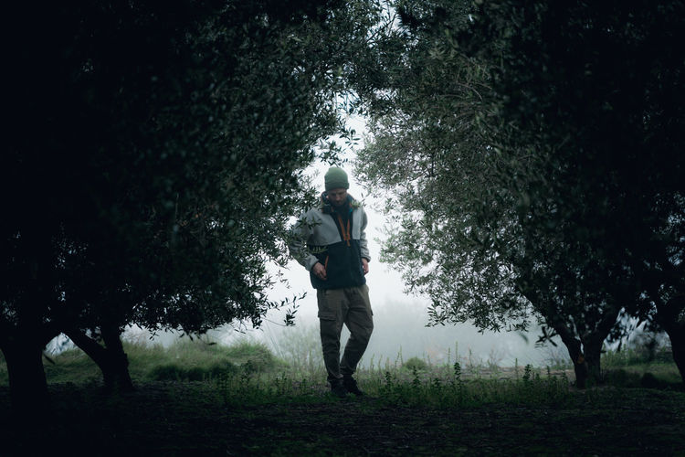 Full length of man standing on field in forest